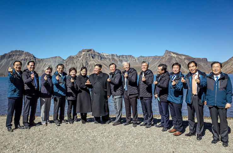 North Korea's leader Kim Jong-un makes a 'finger-heart' for a photo while his wife Ri Sol-ju places her hand below the heart during the visit to Mount Paektu with President Moon Jae-in and South Korean officials, Thursday. Cheong Wa Dae-Yonhap