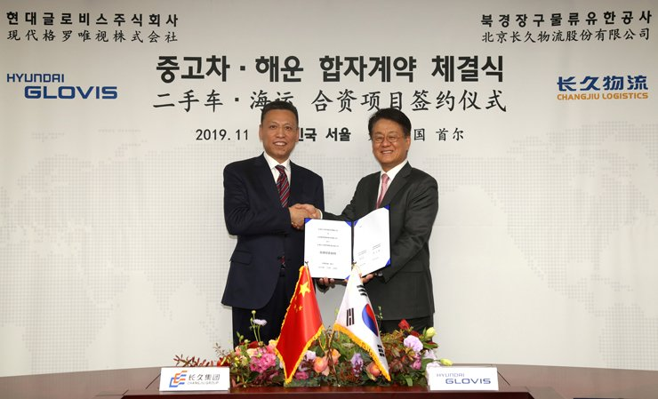 Hyundai Glovis CEO Kim Jung-hoon, right, shakes hands with Changjiu Chairman Bo Shi Jiu after signing agreements on establishing two joint ventures during a ceremony at the former's headquarters in Yeoksam-dong, Seoul, Thursday. Courtesy of Hyundai Glovis