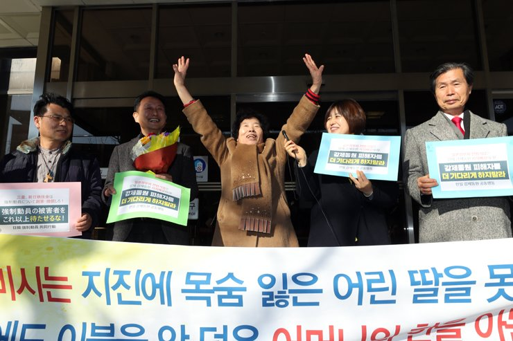 Lee Kyung-ja, a family member of a wartime forced laborer, raises her hands in victory after winning a compensation suit last Dec. 14 against Mitsubishi Heavy Industries in an appeals ruling at Gwangju District Court. / Yonhap
