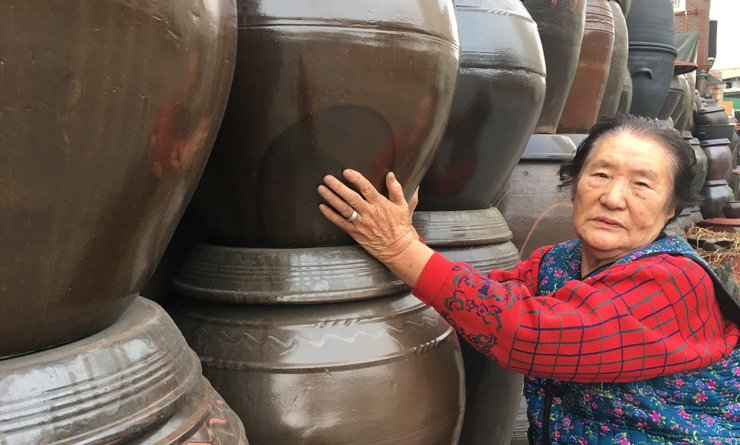 Shin Yeon-geun, 82, stands with the pots lined up outside her shop at the entrance of the Haebangchon area in Seoul. Hansin Onggi, which opened in 1967, has been designated this year as one of the city's Future Heritages. / Korea Times photo by Kim Bo-eun