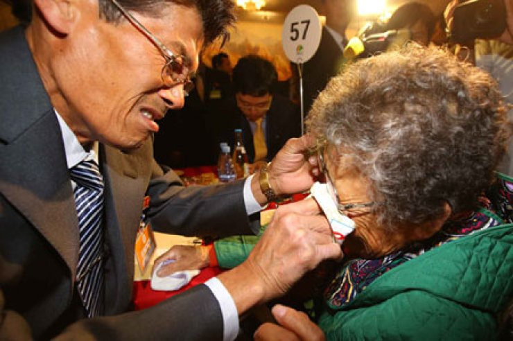 Jeong Geon-mok, 64, one of the 25 men kidnapped by North Korea in the 1972 abduction of the South Korean trawler, Odaeyang, wipes the tears from his mother's face, Lee Bok-soon, 88, at Mount Geumgang, North Korea, Saturday. / Yonhap
