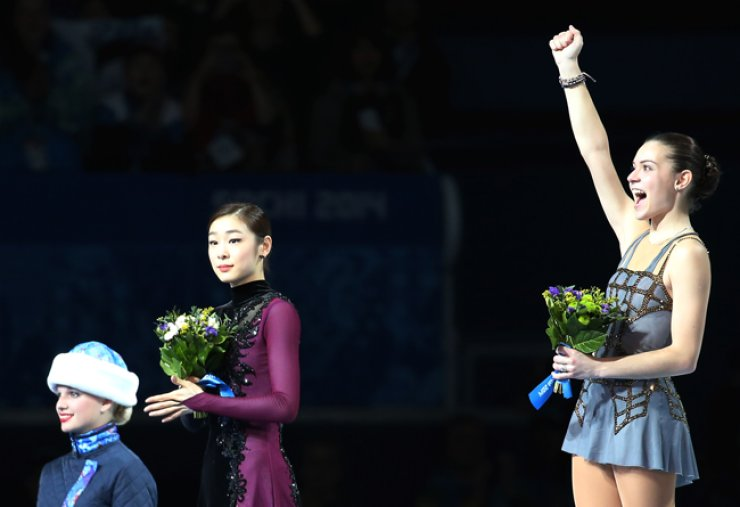 Silver medalist Kim Yu-na applauds figure skating gold medalist Adelina Sotnikova during the 2014 Sochi Olympics medal ceremony. / Korea Times file