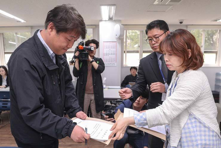 A Korea Kindergarten Association (KKA) official hands over  documents to the Seoul Metropolitan Office of Education staff, appealing the education office's decision to revoke the organization's license at KKA's building in Yongsan, Seoul, April. / Korea Times photo by Seo Jae-hoon