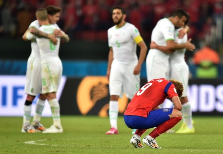 Korea's Son Heung-min squats down on the pitch as Algerian players celebrate their 4-2 win in their Group H match at the Estadio Beira-Rio in Porto Alegre, Brazil. / AP-Yonhap