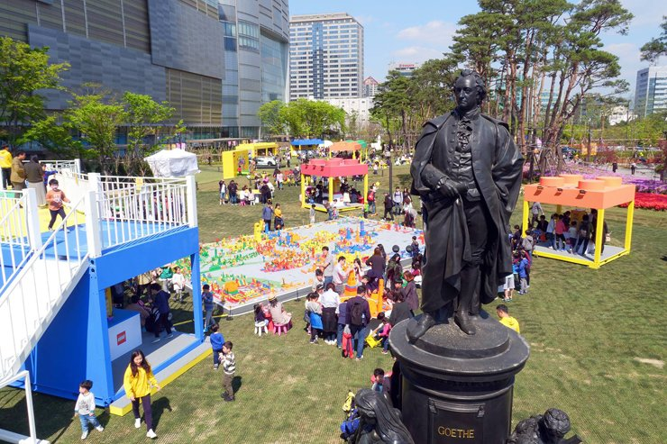 Parents and children play with LEGO bricks during a LEGO festival at a park in front of Lotte World Tower in Jamsil, Seoul, April 22. Lotte Corporation said it is holding various events for those who visit the tower during the golden week holidays. / Courtesy of Lotte Corporation