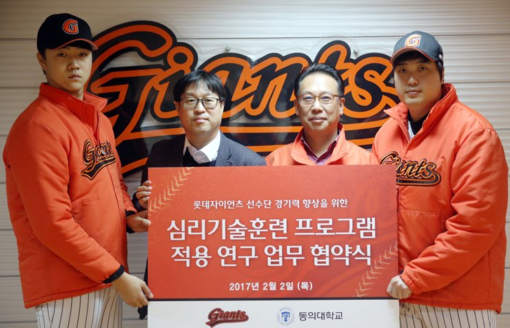 Lotte Giants general manager Lee Yoon-won, second from right, and professor Shin Jung-taek of Busan-based Dong-Eui University, second from left, pose after signing a contract on Feb. 2 to implement a year-long sports psychology program to help the Giants' players build mental toughness. / Yonhap