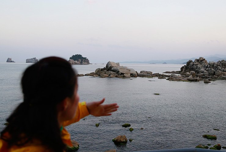 In this Oct. 23, 2018, photo, a tour guide gestures as she explains about a beach where people can see South Korea on the distant horizon at the Mount Kumgang resort area in North Korea. AP