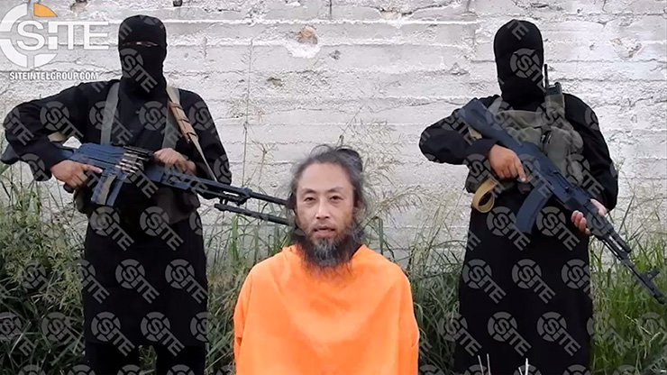 This video image released on July 31 and provided courtesy of SITE Intelligence Group shows Japanese national, Yasuda Jumpei, appealing for his release as two armed men stand behind him at an unknown location in Syria on the July 25. AFP