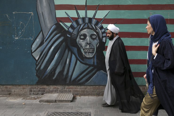 A cleric and a woman walk past an anti-U.S. mural painted on the wall of the former U.S. Embassy in Tehran, Iran, Tuesday. / AP