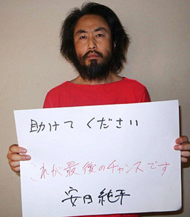 In this undated picture provided by Japan's Jiji Press news agency on May 30, 2016, Japanese freelance journalist Jumpei Yasuda holds a banner with a handwritten message in Japanese at an undisclosed location. A Japanese journalist kidnapped in Syria more than three years ago is believed to have been released, the government said on October 23. Jumpei Yasuda, a 44-year-old freelancer, was seized in the war-torn country in June 2015, and appeared in a rare video released by a militant group over the summer warning that he was in a bad situation. AFP