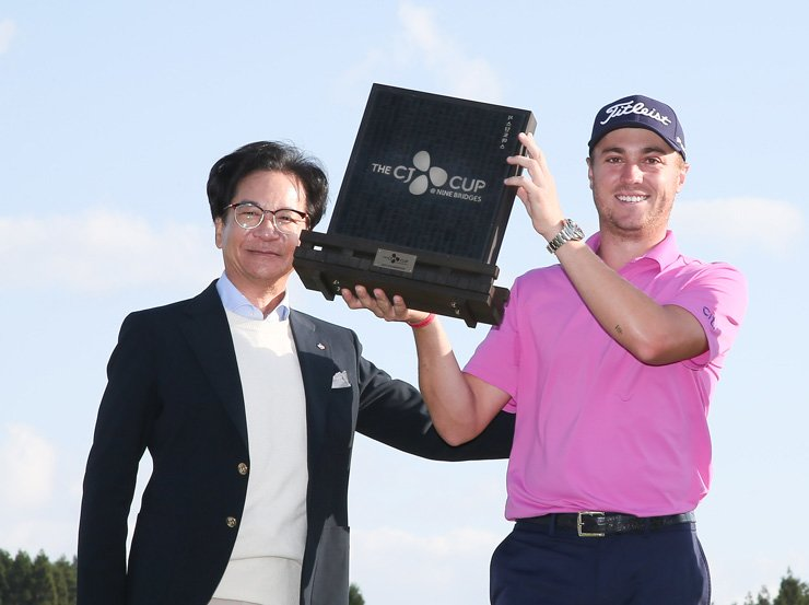 American golfer Justin Thomas, right, and CJ Group Chairman Lee Jay-hyun pose with a trophy as Thomas claimed the inaugural CJ Cup @ Nine Bridges title on Jeju Island, Sunday. / Courtesy of JNA GOLF