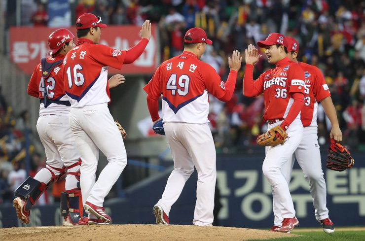 The Kia Tigers players celebrate after winning Game 4 of the Korean Series at the Jamsil Baseball Stadium in Seoul, Sunday. / Yonhap