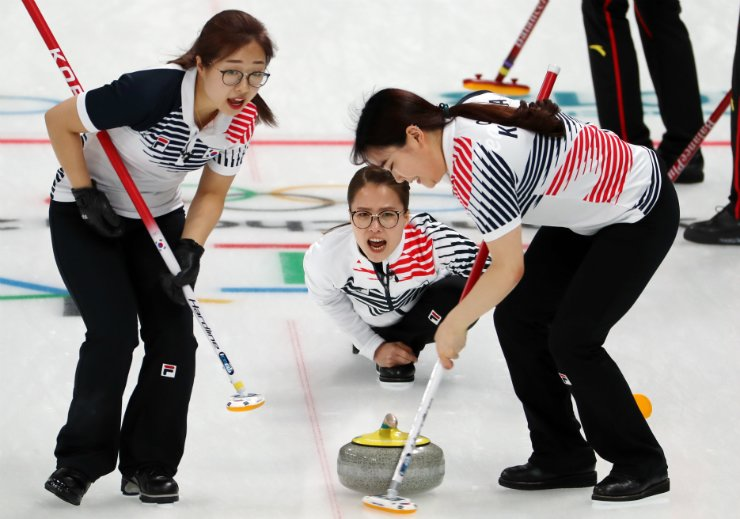 Korea's skip Kim Eunjung, center, throws a stone during a women's curling match against China at the 2018 Winter Olympics in Gangneung, Sunday. Korea defeated China 12-5. / Yonhap