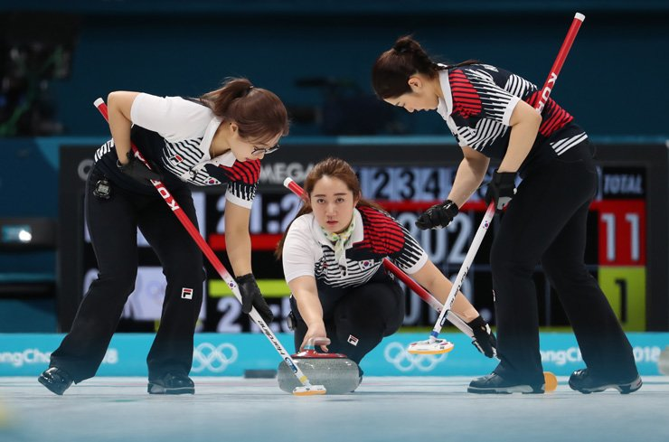 Korea's Kim Yeong-mi, center, releases a stone during a women's curling match against the Olympic Athletes of Russia at the Gangneung Curling Center, Wednesday. Korea won 11-2. / Yonhap