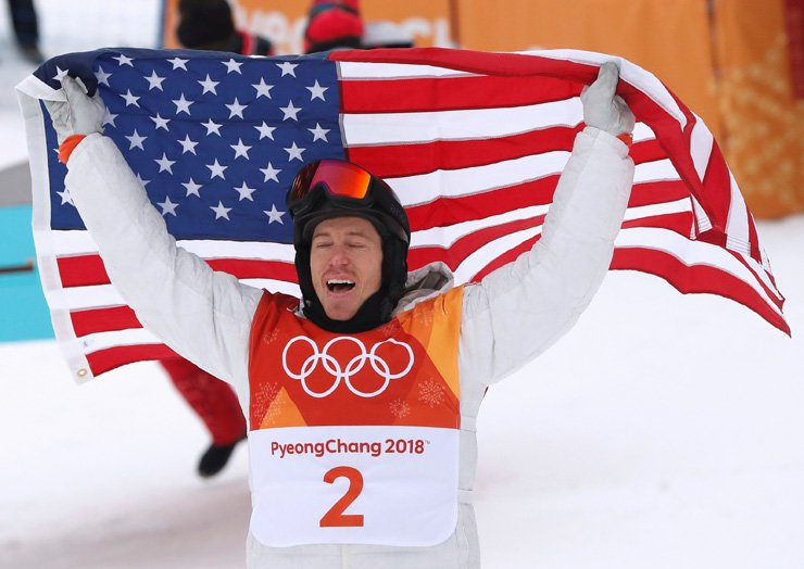 American snowboarder Shaun White celebrates his win as he holds the U.S. flag after winning the men's halfpipe final of the PyeongChang Winter Olympics at Phoenix Snow Park in PyeongChang, Feb. 14. / Reuters-Yonhap