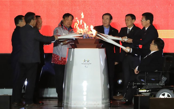 Representatives holding eight torches, including Paralympic and government officials join to create a single flame during the torch lighting ceremony for the PyeongChang Winter Paralympics at Olympic Park in Seoul, Saturday. / Yonhap