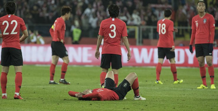 Korean national football team forward Song Heung-min, center, lays on the ground after losing the football friendly against Poland at Silesian Stadium in Chorzow, Poland, Tuesday. / Yonhap