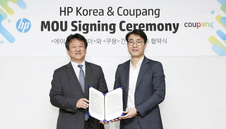 Coupang Senior Director James Lee, right, poses with HP Korea Country Managing Director Kim Dae-hwan after signing a business partnership at the Coupang headquarters in southern Seoul, Wednesday. Courtesy of Coupang