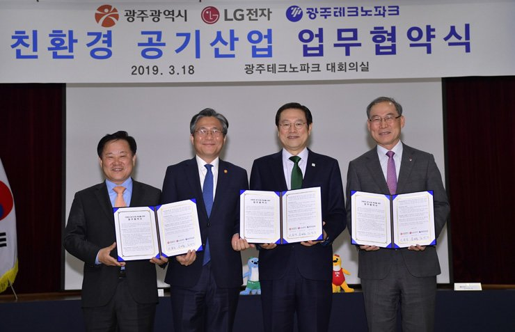 Song Dae-hyun, right, president of home appliance and air systems at LG Electronics, poses with Gwangju Techno Park President Kim Sung-jin, left, Industry Minister Sung Yun-mo, second from left, and Gwangju Mayor Lee Yong-seop after signing a memorandum of understanding to foster the air purifier industry in Gwangju at the Gwangju Techno Park industrial complex, Monday. / Courtesy of LG Electronics