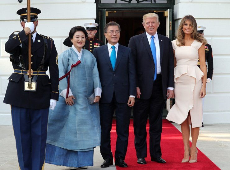 South Korean President Moon Jae-in, center, poses with U.S. President Donald Trump, second from right, in their first meeting at the White House, Washington, D.C., Thursday, along with South Korean first lady Kim Jung-sook, second from left, and U.S. first lady Melania Trump. / Yonhap