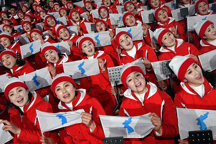 North Korean cheerleaders wave unification flags showing the eastern islets of South Korea during Team Korea's ice hockey game against Sweden at the Gwandong Ice Hockey Center in Gangneung, Monday. / Yonhap