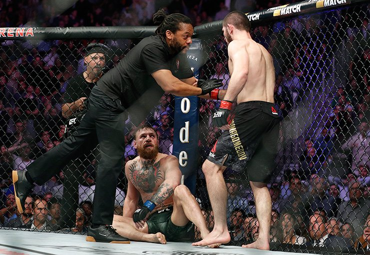 Khabib Nurmagomedov, right, is held back by referee Herb Dean after defeating Conor McGregor, bottom, in a lightweight title mixed martial arts bout at UFC 229 in Las Vegas, Saturday. AP