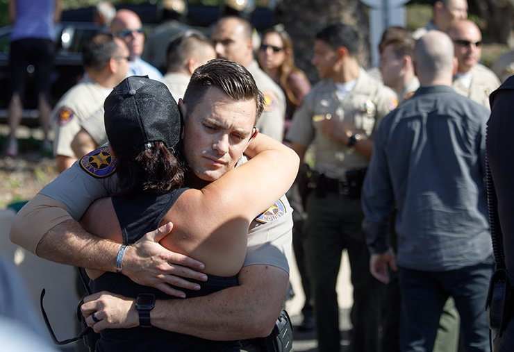 Law enforcement officers and workers react after the hearse carrying the body of Sergeant Ron Helus arrives at the medical examiner's office in Ventura, Calif., Nov. 08. Thirteen people were killed and several wounded in the mass shooting at the Borderline Bar & Grill. EPA