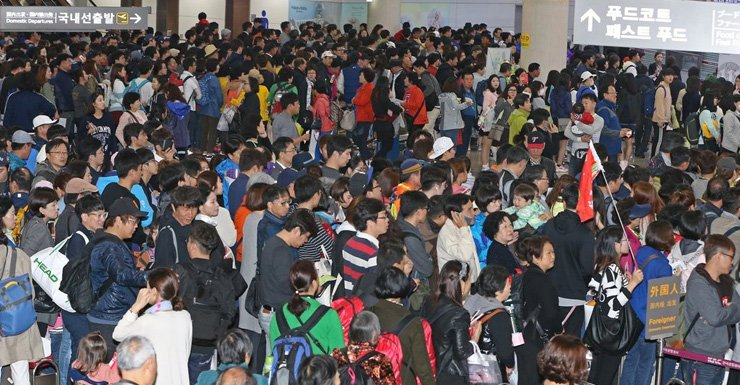 Jeju International Airport is crowded with tourists. Jeju residents are protesting the government's project to build a new airport, saying the overwhelming number of tourists are already causing too many problems on the island. / Yonhap