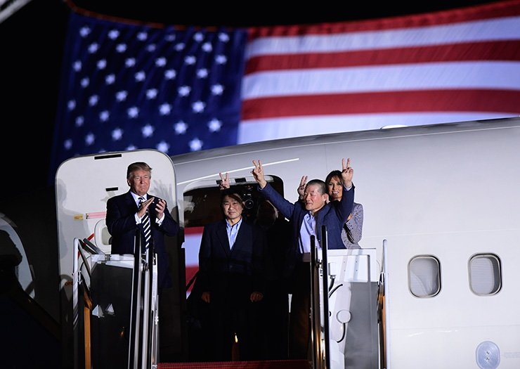 US President Donald Trump applauds as U.S. detainee Kim Dong-chul, second from right, gestures upon his return with Kim Hak-song (behind) and Tony Kim, center, after they were freed by North Korea, at Joint Base Andrews in Maryland, Thursday (local time). / AFP