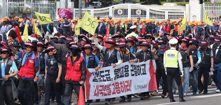 Protesters urge construction companies to hire more Koreans over foreigners as they march around Gwanghwamun Square in central Seoul, Wednesday. / Yonhap