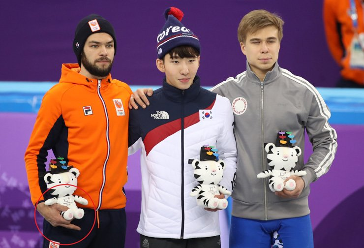Sjinkie Knegt of the Netherlands, left, stands next to Lim Hyo-jun of South Korea, center, and Semion Andreyevich Elistratov of Russia (OAR) after the men's 1,500-meter final at Gangneung Ice Arena, Saturday. / Yonhap