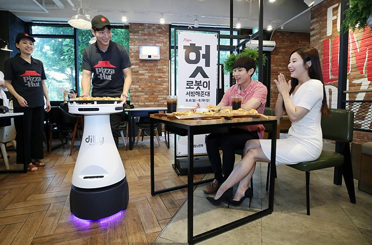 A Pizza Hut employee serves a pizza to customers with the aid of robot 'Dilly Plate' at the company's Mok-dong store in western Seoul, Wednesday. Yonhap