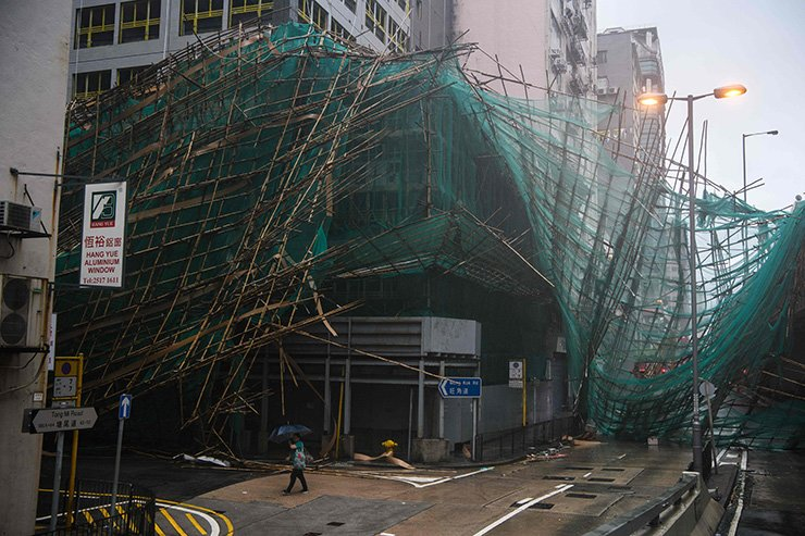 A woman uses her umbrella as she walks past collapsed bamboo scaffolding hanging from a building during Super Typhoon Mangkhut in Hong Kong on Sept. 16. Typhoon Mangkhut rocked Hong Kong en route to mainland China on September 16, injuring scores and sending skyscrapers swaying, after killing at least 30 people in the Philippines and ripping a swathe of destruction through its agricultural heartland. AFP