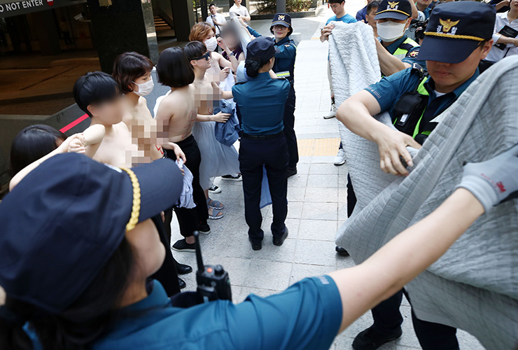 Police approach a group of topless women to cover them with blankets at a rally near Facebook headquarters in Seoul on Saturday. Yonhap