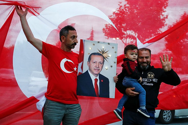 A supporter of AK Party holds a picture of Turkish President Tayyip Erdogan outside the party's headquarters in Istanbul, Turkey, Sunday (local time). Reuters