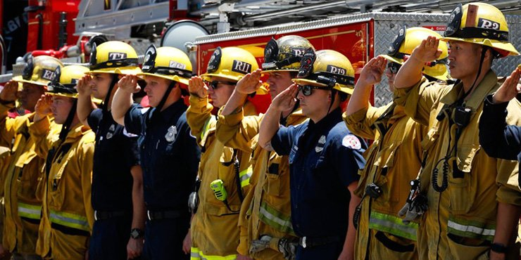 Firefighters salute during a procession for Fire Capt. Dave Rosa who was killed after he was shot responding to an emergency at a senior home in Long Beach, California, June 25 (local time). AP