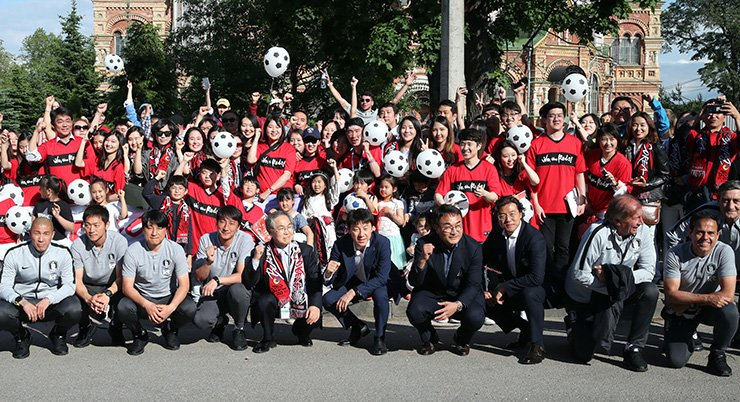 South Korea national football team head coach Shin Tae-yong, center, poses for a group photo with national team staff and South Korean residents after arriving at New Peterhof Hotel in Saint Petersburg, Russia, Tuesday. Yonhap