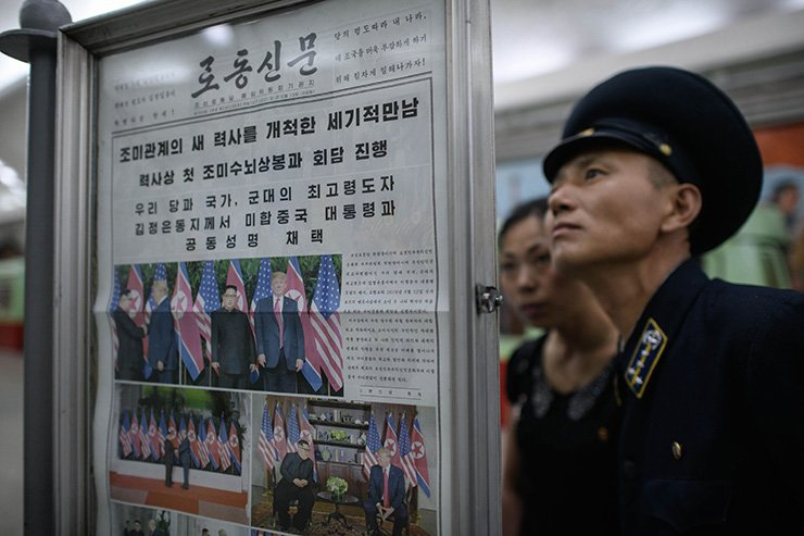 A conductor reads the latest edition of the Rodong Sinmun newspaper showing images of North Korean leader Kim Jong-un meeting with U.S. president Donald Trump during their summit in Singapore, at a news stand on a subway platform of the Pyongyang metro on Wednesday. AFP