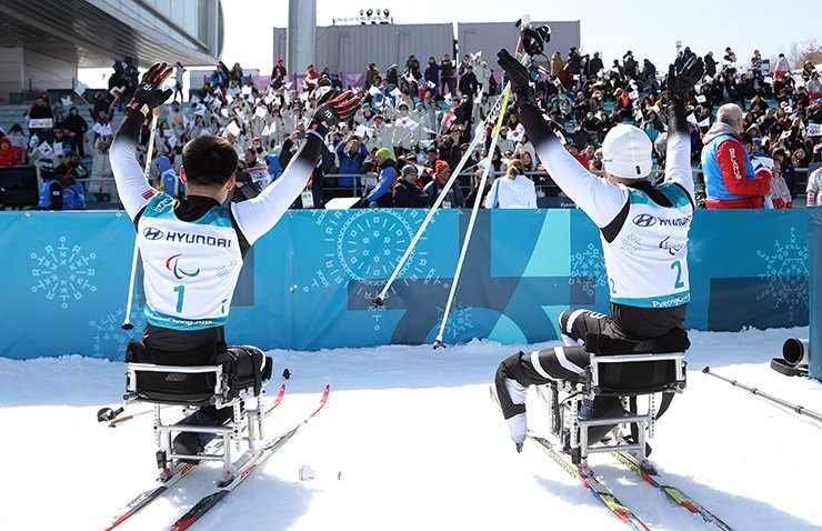 North Korean para athletes Kim Jong-hyon, left, and Ma Yu-chol wave to the audience after competing in the men's 15-kilometer sitting cross-country skiing event at Alpensia Biathlon Center in PyeongChang, Sunday. / Yonhap