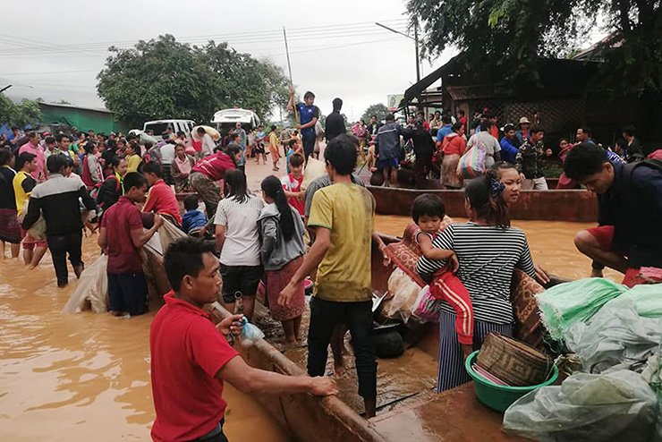 This handout photo taken on July 24 and received from Attapeu on July 25 shows displaced residents arriving by boat in floodwaters in Attapeu province after a dam collapsed on July 23. AFP