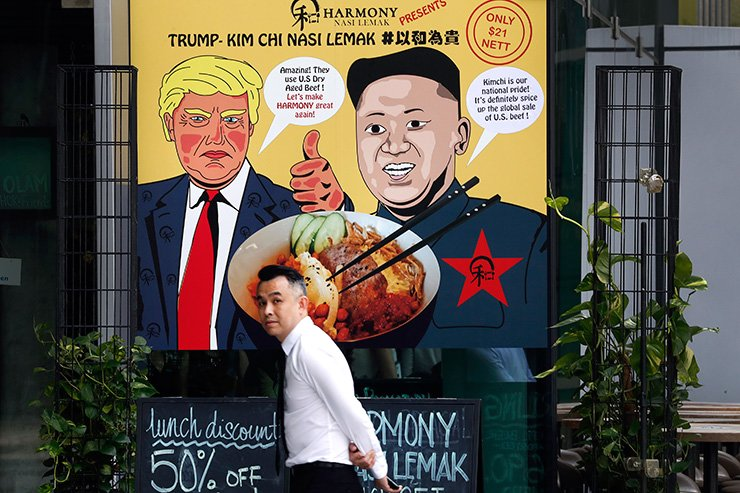 In this June 7, 2018, photo, a man walks past an advertisement board of cartoon caricatures of U.S. President Donald Trump and North Korean leader Kim Jong-un which are supposed to be the inspiration behind a local dish, the 'Trump-Kim Chi Nasi Lemak' at a mall, in Singapore. AP