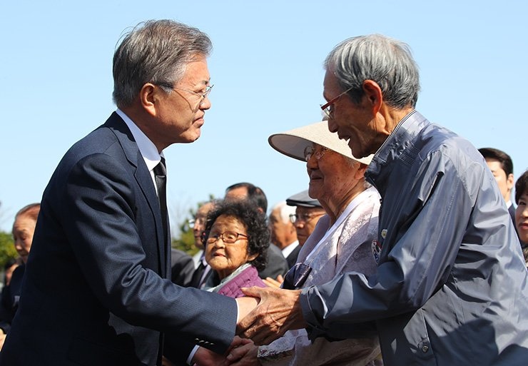 President Moon Jae-in shakes hands with the families of Jeju massacre victims at the 4.3 Peace Park on Jeju Island, Tuesday. / Yonhap