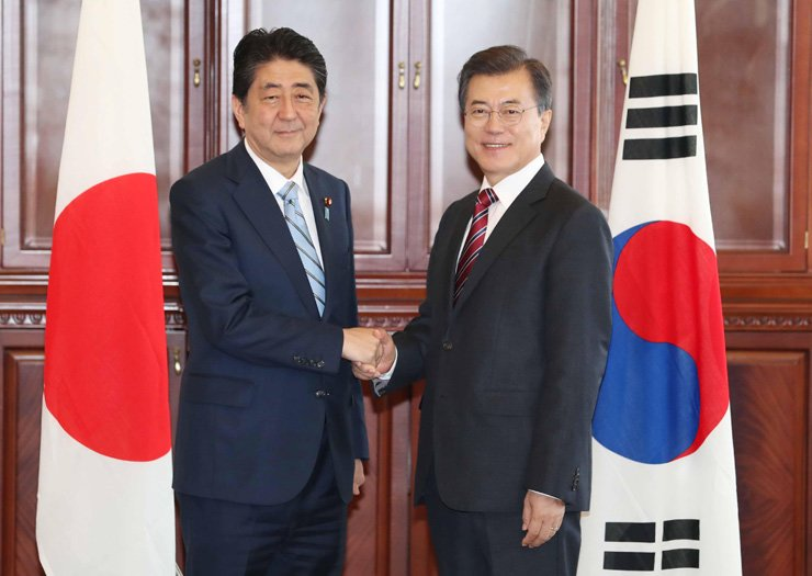 President Moon Jae-in, right, shakes hands with Japanese Prime Minister Shinzo Abe before their summit at Far Eastern Federal University in Vladivostok, Russia, Thursday. / Korea Times photo by Koh Young-kwon