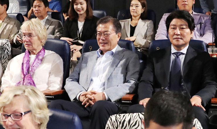 President Moon Jae-in, center, watches 'A Taxi Driver,' a movie based on the true story of  the late Jurgen Hinzpeter, a German journalist who covered the Gwangju pro-democracy movement in 1980, at a local theater in Seoul, Sunday, together with Edeltraut Brahmstaedt, left, the widow of Hinzpeter, and Song Kang-ho, right, the actor who played the main character in the movie. / Courtesy of Cheong Wa Dae