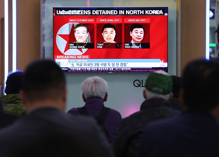 In this May 3, 2018 photo, people watch a TV news report screen showing portraits of three Americans, Kim Dong-chul, left, Tony Kim and Kim Hak-song, right, detained in the North Korea, at the Seoul Railway Station in Seoul. U.S. President Donald Trump says Secretary of State Mike Pompeo is on his way back from North Korea with three American detainees, saying they 'seem to be in good health.' / AP