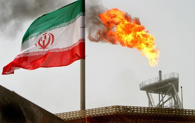 A gas flare on an oil production platform in the Soroush oil fields is seen alongside an Iranian flag in the Persian Gulf, Iran, July 25, 2005. / Reuters