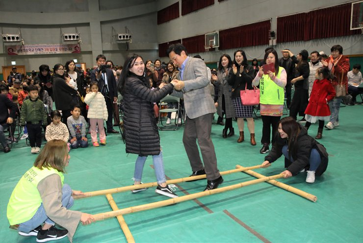 Jeju Governor Won Hee-ryong plays traditional Filipino game Tinikling with multicultural family members prior to Lunar New Year' day at Namgwang Elementary School in Jeju on Feb. 6. / Courtesy of Jeju Special Self-Governing Province