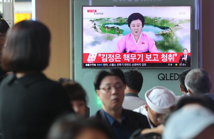 Citizens in Seoul Station watch news showing a North Korean newsreader announcing that Pyongyang successfully carried out a hydrogen bomb test, Sunday. / Yonhap