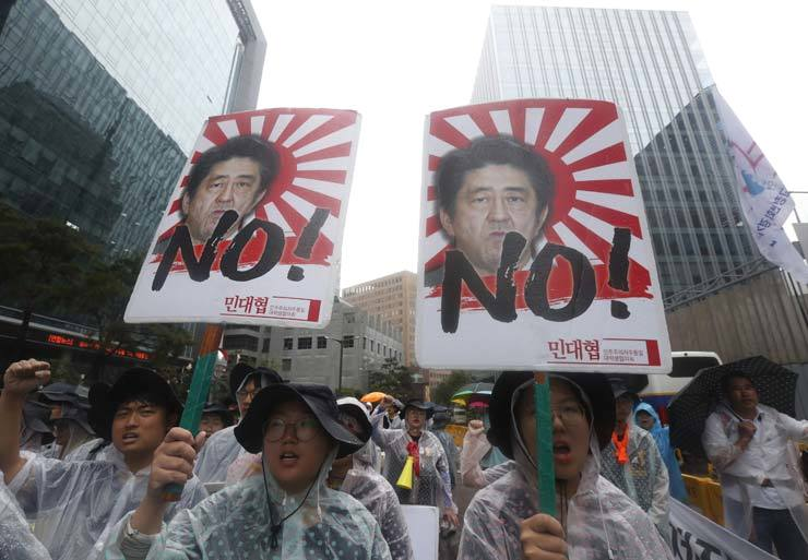 Korean protesters with images of Japanese Prime Minister Shinzo Abe shout slogans during a rally to mark the Korean Liberation Day from Japanese colonial rule in 1945, in front of the Japanese Embassy in Seoul, South Korea, Thursday. / AP-Yonhap