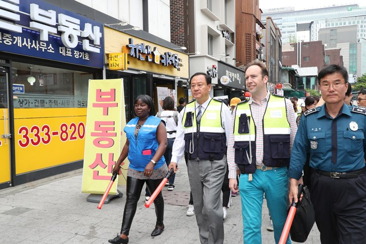Mapo-gu Office Head Yoo Dong-gyun, second from left, patrols around the Hondae area with foreigners recently picked for volunteer patrol company program in the town, last Friday. Courtesy of Mapo-gu Office